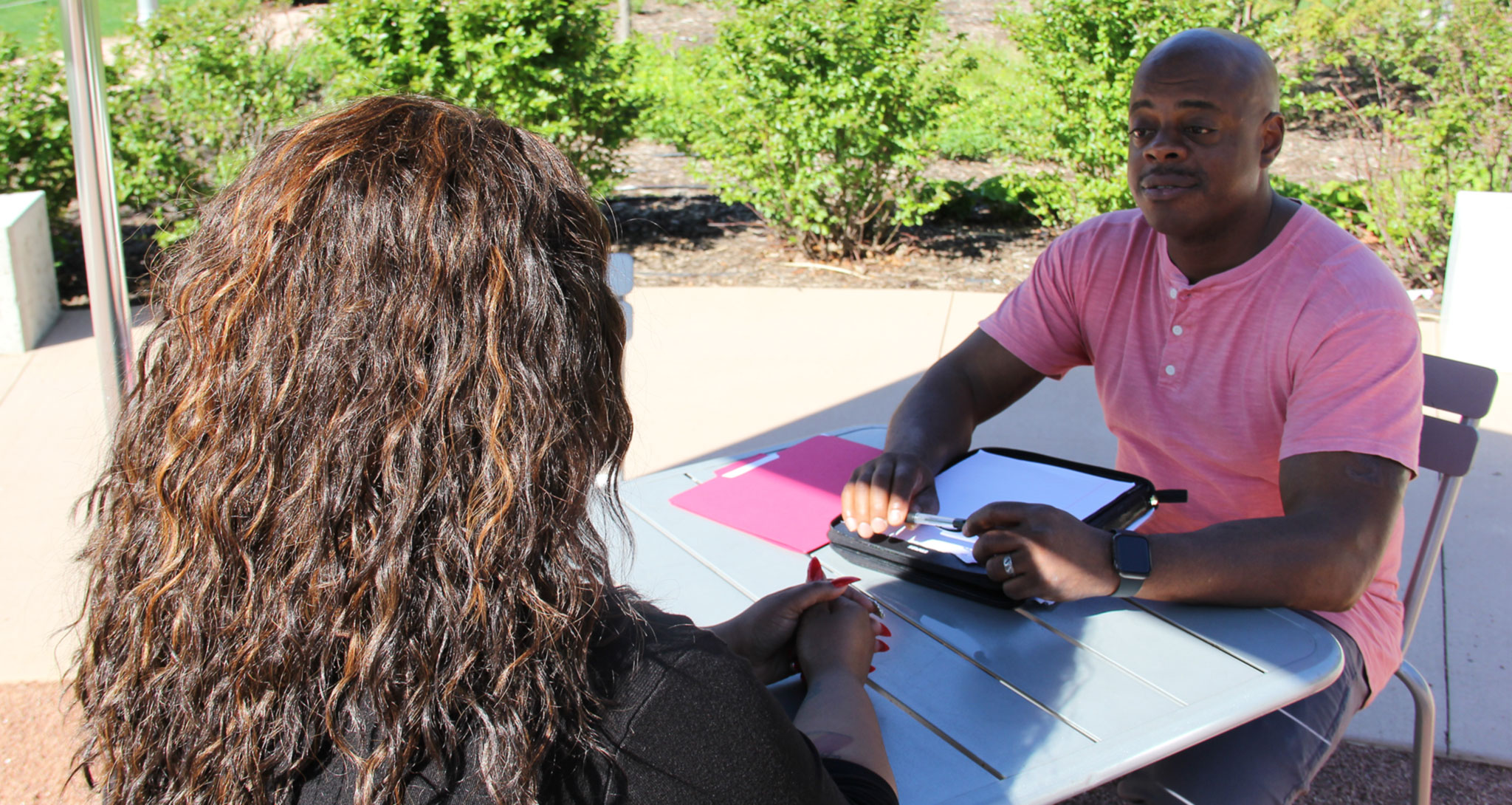 Tyrone Patterson, a psychiatric social worker and mental health survivor, meeting with a client in the park.