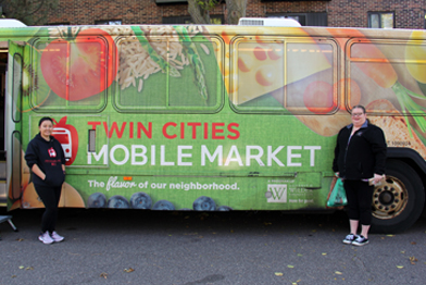 Two women standing in a front a Twin Cities Mobile Market bus