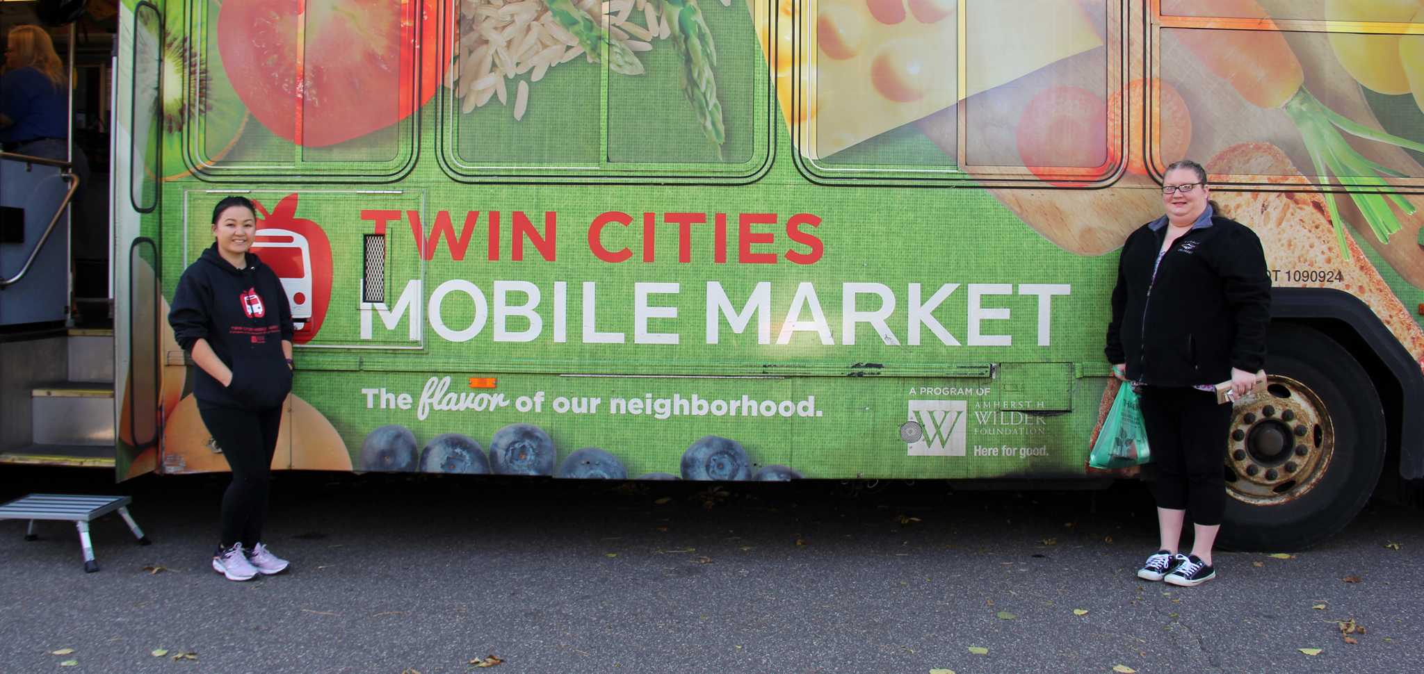 Two women standing in front of a Twin Cities Mobile Market bus