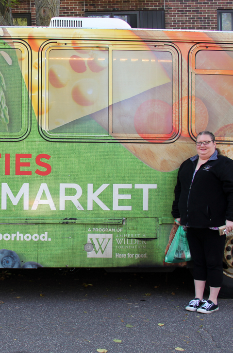 A woman standing in front of a Twin Cities Mobile Market bus