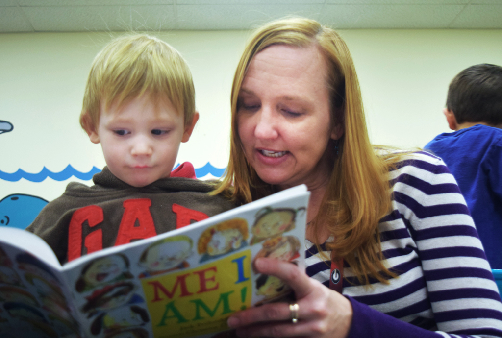 Childcare provider reads a boy a book