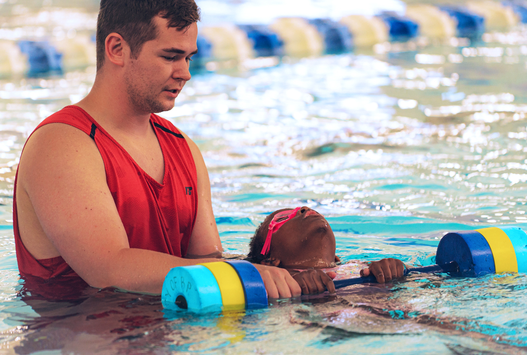 A child and her swim instructor in a pool